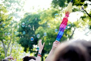 people holding multi colored balloons during daytime