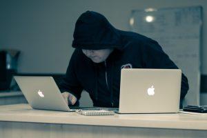 man in black hoodie using macbook
